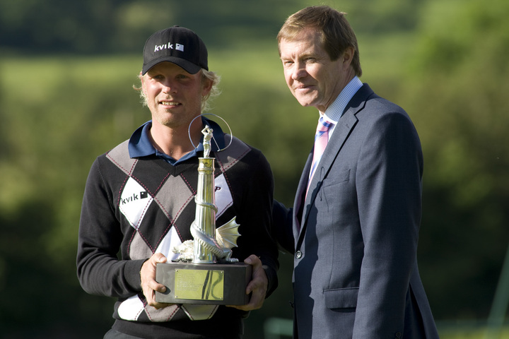 poses with the trophy alongside George O'Grady the chief executive of the european tour after winning the European Tour Welsh Open golf tournament.